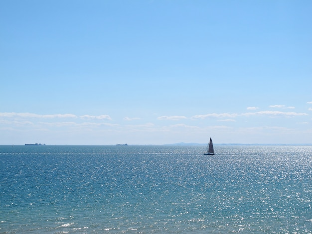 View of sparkle sea water have sailboat on blue sky at sandringham beach
