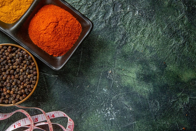 Sopra la vista delle ciotole di spezie riempite con peperone rosso e misuratore di zenzero giallo sulla superficie dei colori della miscela