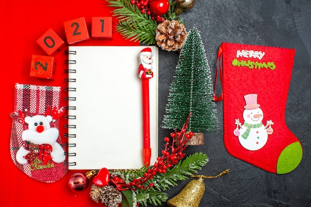 Above view of spiral notebook decoration accessories fir branches xsmas sock numbers on a red napkin and christmas tree on dark background
