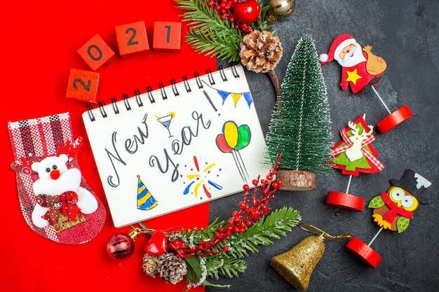Above view of spiral notebook with new year writing and drawings decoration accessories fir branches xsmas sock numbers on a red napkin and christmas tree on dark background