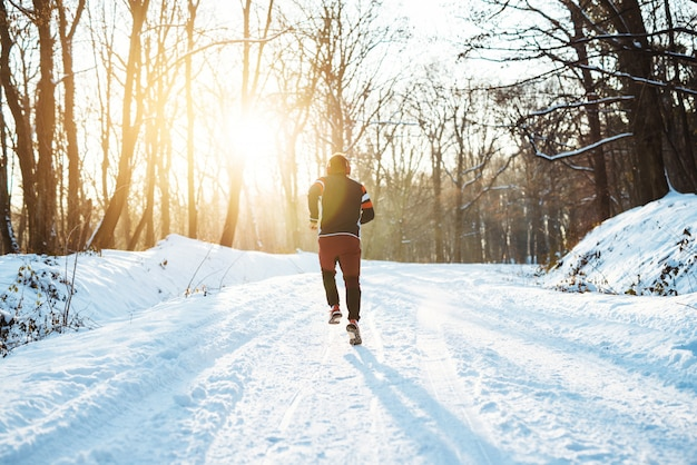 View of sportsman running in snowy forest at wonderful sunrise