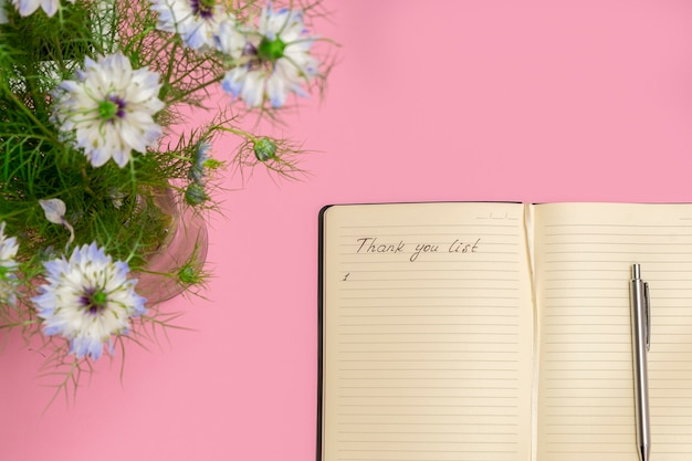 Above view of spring flowers and open gratitude journal