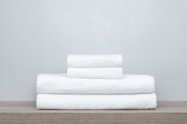 View of a stack of neatly folded white bath towels on a wooden shelf.