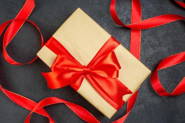 Sopra la vista di bellissimi doni impilati con nastro rosso su sfondo scuro