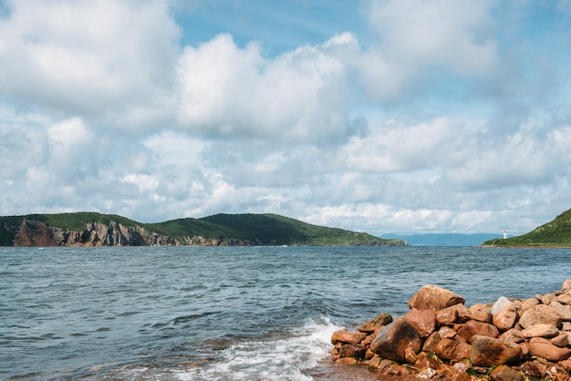 View of stark strait, coastal stones, sea and sky with clouds. travel and nature theme.
