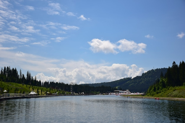 A view of a summer resort in the mountains with a large lake and comfortable places for recreation and walks along its shores. against the backdrop of wooded mountains and blue sky