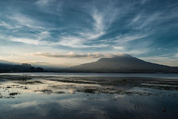 Вид на закат над озером батур возле вулкана батур, область кинтамани, бали, индонезия.