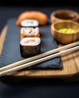 View of sushi rolls, maki, uramaki, nigiri and sashimi set served on stone slate.