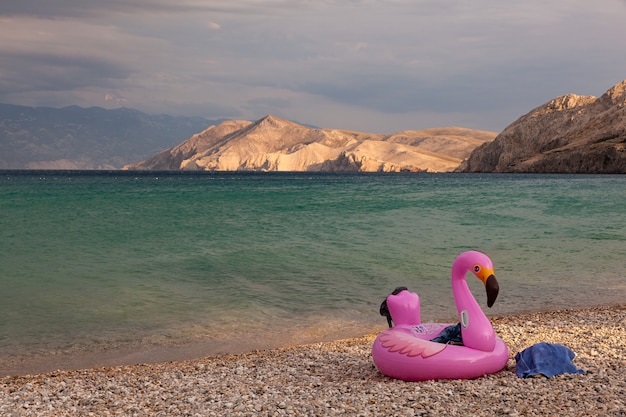 View of a swimming inflatable ring with flamingo design on the beach of baska, croatia