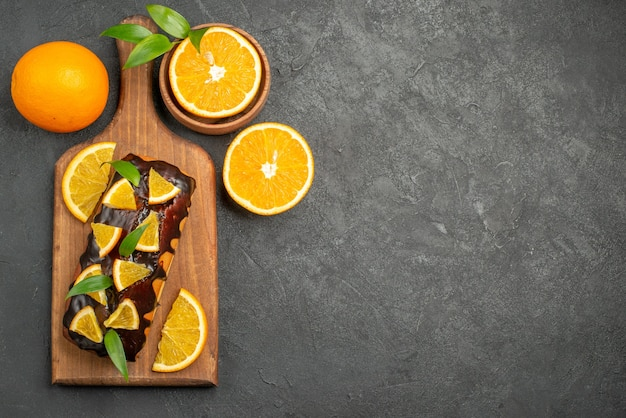 Above view of tasty cakes whole and cut oranges on cutting board on black table