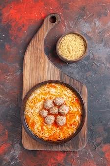 Sopra la vista di gustosa zuppa di pollo con tagliatelle su tagliere di legno e pasta cruda in una piccola ciotola su sfondo scuro