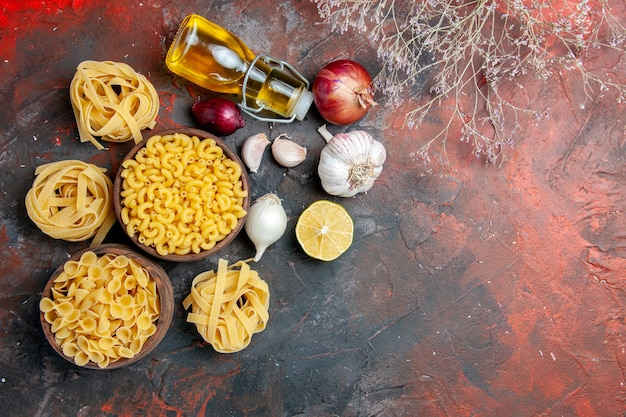 Above view of tasty dinner preparation with uncooked pastas in various forms and garlic fallen oil bottle garlic lemon on mixed color table