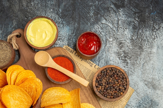 Above view of tasty homemade chips cut potato slices on wooden cutting board and different spices on newspaper on gray table