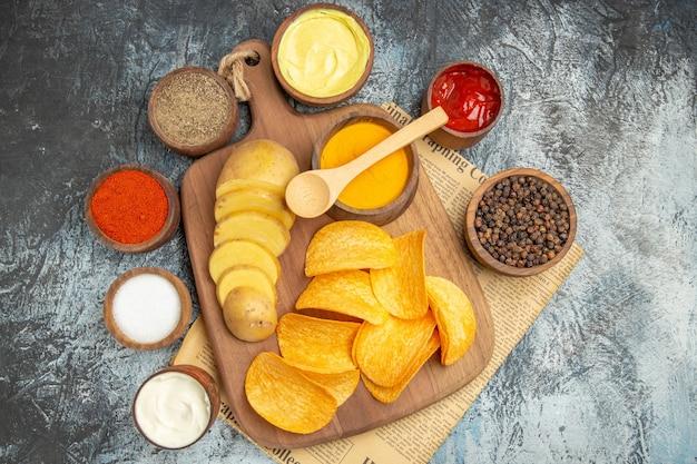 Sopra la vista di gustose patatine fatte in casa tagliate le fette di patate sul tagliere di legno e diverse spezie sul giornale sul tavolo grigio
