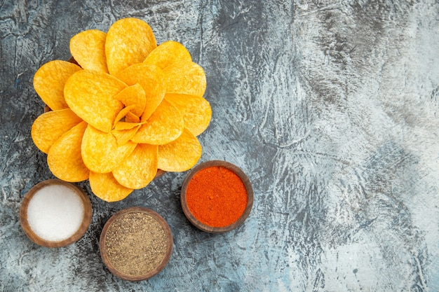 Above view of tasty potato chips decorated like flower shaped and different spices on gray table