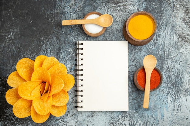 Above view of tasty potato chips decorated like flower shaped different spices with spoons on them and notebook on gray table