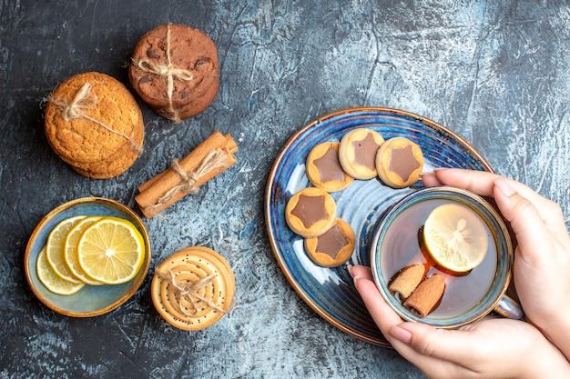 Sopra la vista dell'ora del tè con vari biscotti e mano che tiene una tazza di tè nero con cannella su un vassoio blu su sfondo scuro
