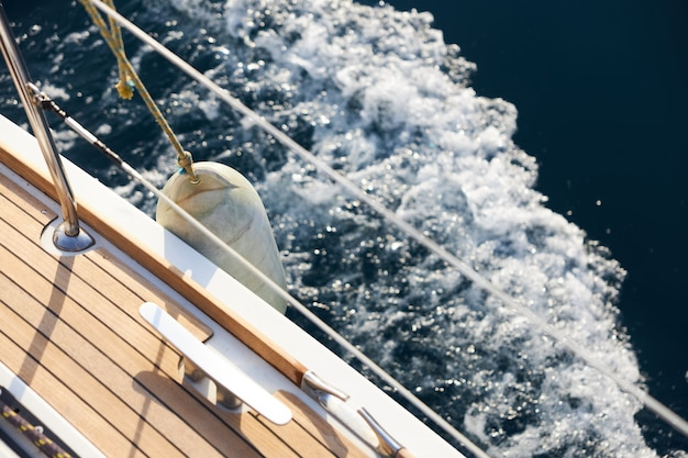 View of the teak deck of a sailing yacht moving on a calm surface of the sea