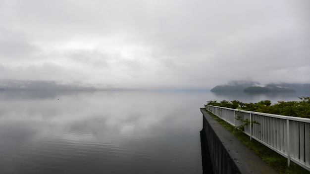 View of terraced with white fence into the lake in the thick fog and low light.