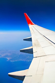 A view though an airplane window where one can see the wing, sea and islands