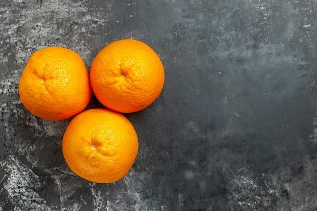 Sopra la vista di tre arance fresche organiche naturali sul lato destro su sfondo scuro