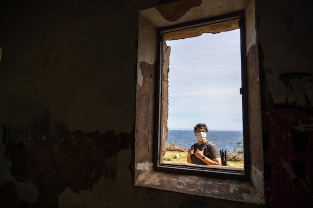 マスクをした男の廃屋の窓越しに見る