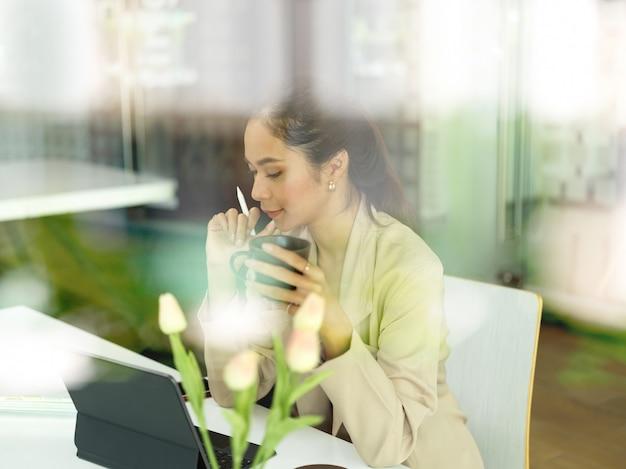 Вид через стеклянное окно на офисную работницу, которая делает перерыв на кофе во время работы с цифровым планшетом на рабочем месте