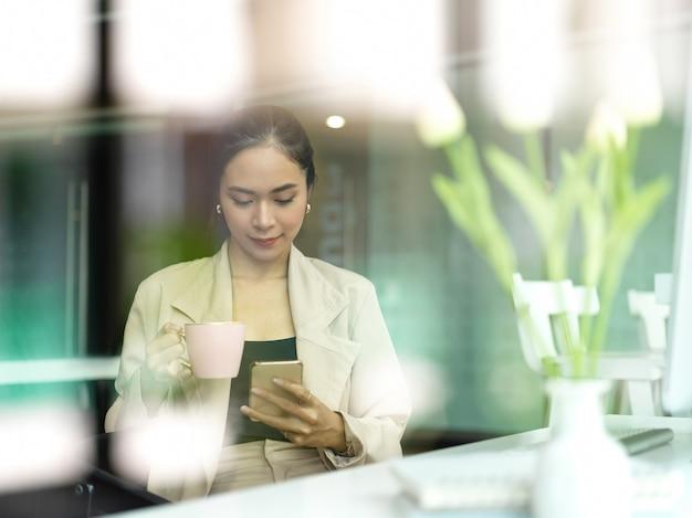 Вид через стеклянное окно офисного работника-женщины, отдыхающего с чашкой напитка и смартфоном в офисной комнате