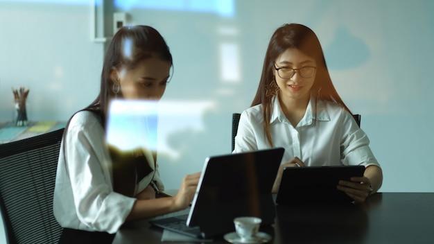 Вид через стеклянное окно на двух офисных работниц, консультирующихся по их проекту в конференц-зале