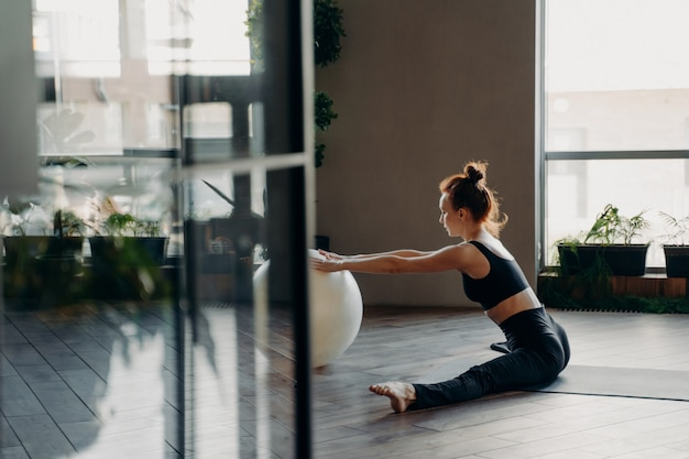 View through open glass door of flexible redhead slender female in active wear sitting in twine on mat with hands laying on big fitball while performing stretching exercises in gym or fitness studio