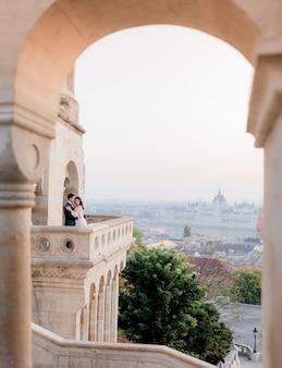 Вид через каменную арку города будапешта и крошечный силуэт влюбленной пары