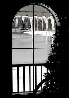 옆에 크리스마스 트리가 있는 얼어붙은 강에서 창을 통해 보기