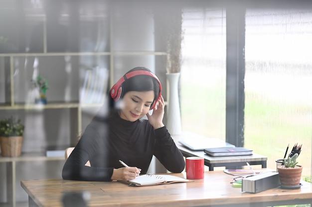 Вид через окно симпатичная женщина-дизайнер слушает музыку и работает в современном офисе.