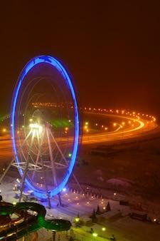 겨울 밤에 푸른 조명으로 관람차 회전 목마를 봅니다.