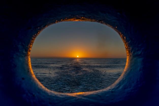 Вид на закат через иллюминатор на корме корабля