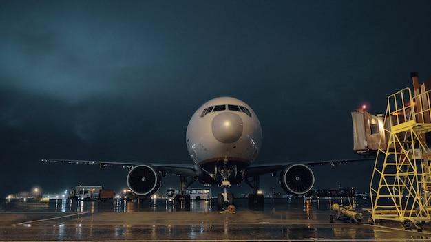 夜に空港に停車している旅客機のコックピットとエンジンを見る