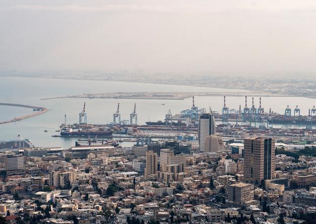 Вид на порт хайфы в израиле в пасмурный день. промышленная часть хайфы с доками и паромами. здания приморского города. туристические достопримечательности израиля. залив в средиземном море.