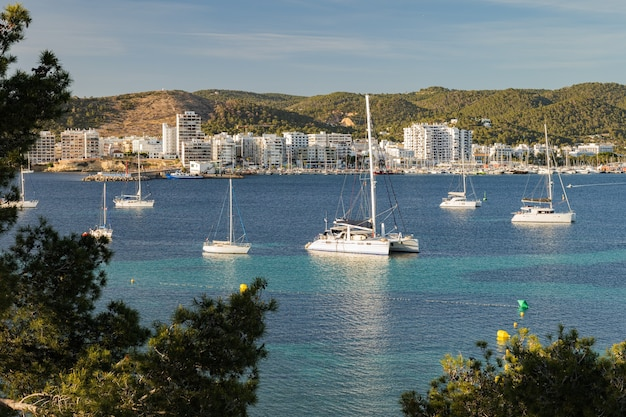 Вид на залив порт-де-сан-антони-де-портмани на побережье ибицы с бирюзовой водой и яхтами на ...
