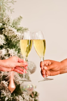 View of a toast with champagne glasses being made by two female hands