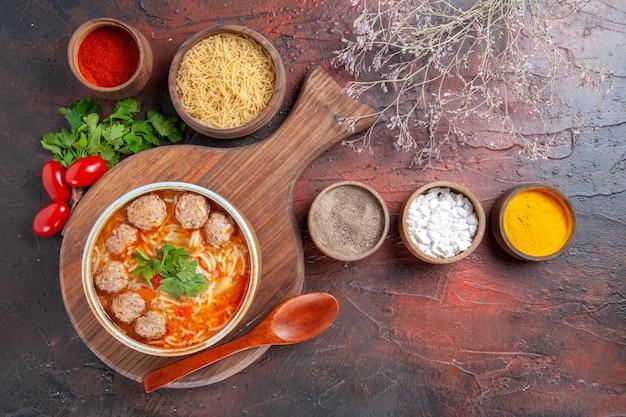 Sopra la vista della zuppa di polpette di pomodoro con tagliatelle in una ciotola marrone e diverse spezie olio bottiglia cipolla aglio su sfondo scuro fotografia stock