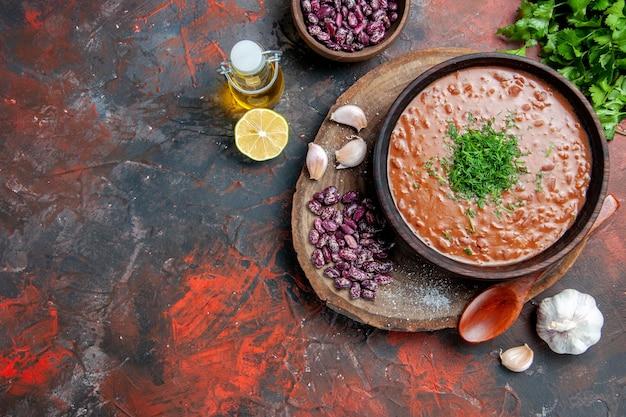 Sopra la vista del cucchiaio di aglio di fagioli di sapone di pomodoro sul tagliere di legno e bottiglia di olio verde limone