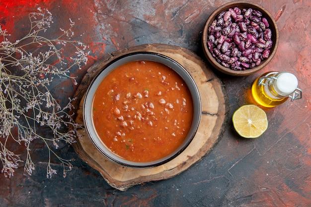 Sopra la vista della zuppa di pomodoro in una ciotola blu su una bottiglia di olio di fagioli vassoio di legno sulla tabella di colore misto