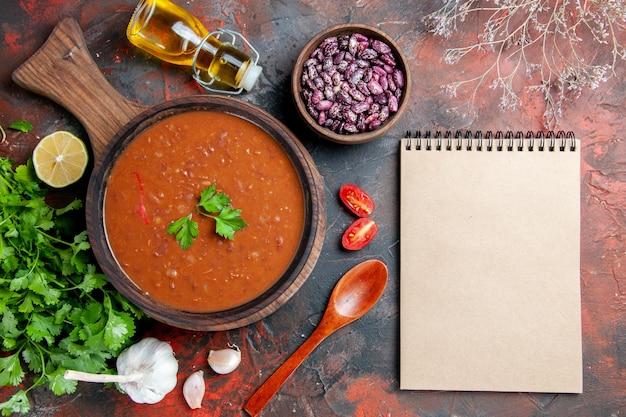 Sopra la vista della zuppa di pomodoro su una bottiglia di olio di fagioli di un tagliere e notebook su una tavola di colori misti