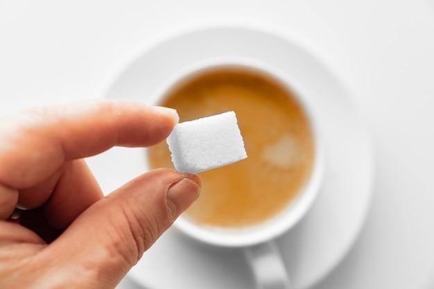 Посмотреть сверху. чашка кофе с молоком и кубическим сахаром в руке. традиционный утренний завтрак. бодрость в ранние утренние восхождения. капучино