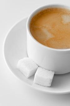 Посмотреть сверху. чашка кофе с молоком и кусочками сахара на блюдце. традиционный утренний завтрак. бодрость в ранние утренние восхождения. капучино