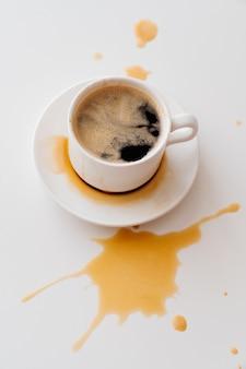 Посмотреть сверху. из чашки кофе разбросать брызги на белом столе. традиционный утренний завтрак. бодрость в ранние утренние восхождения. капучино