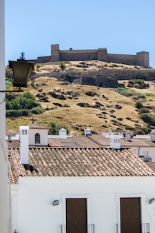 View on top of the hill the castle from the village of aracena, located in spain.