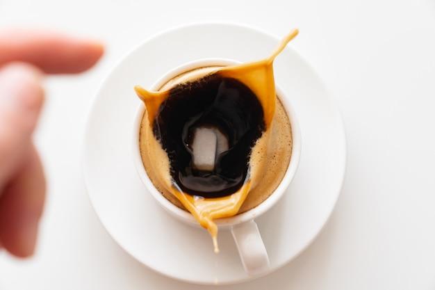Посмотреть сверху. в чашку кофе с молоком бросают кубик сахара и летят брызги. традиционный утренний завтрак. бодрость в ранние утренние восхождения. капучино