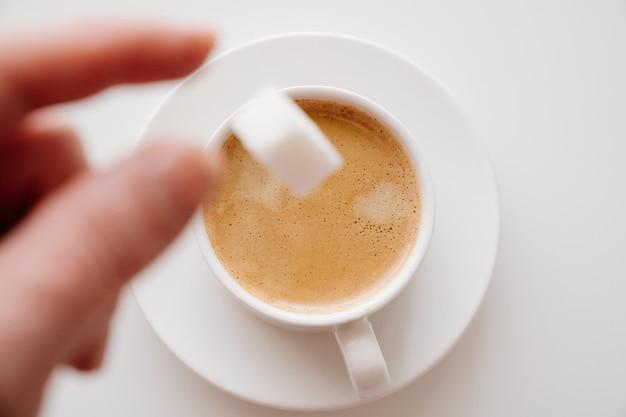 Вид сверху в чашку кофе с молоком бросить кубик сахара
