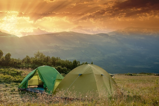 View of tourist tent in mountains at sunrise or sunset. camping background. adventure travel active lifestyle freedom concept. summer vacation.
